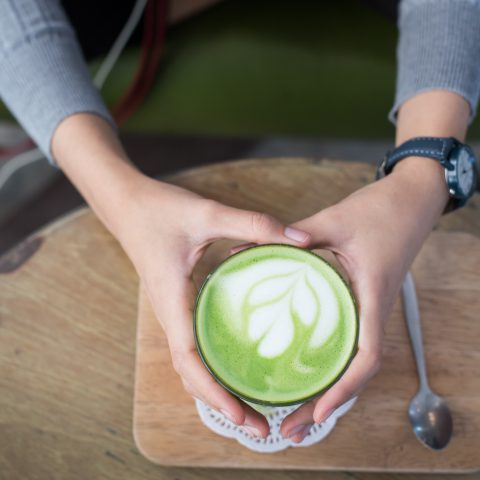 Girl hold Matcha latte by their both hands